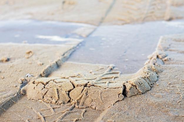 Traces de roue sur le sable.