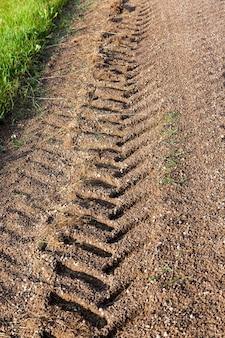 Traces de roues de tracteur ou de camion sur le sable après la pluie
