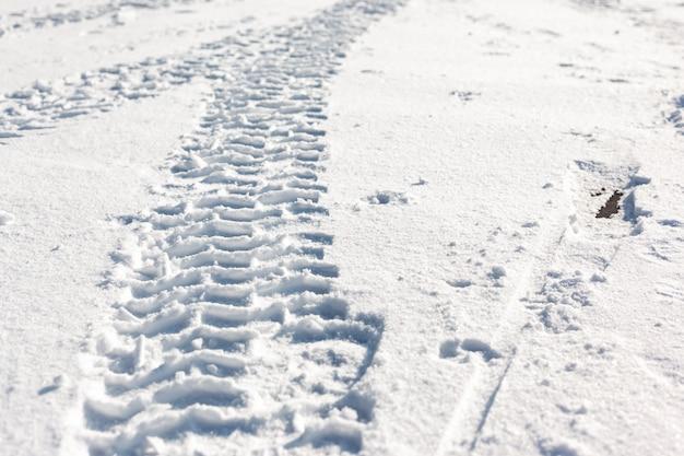 Des traces de roues de voiture dans la neige