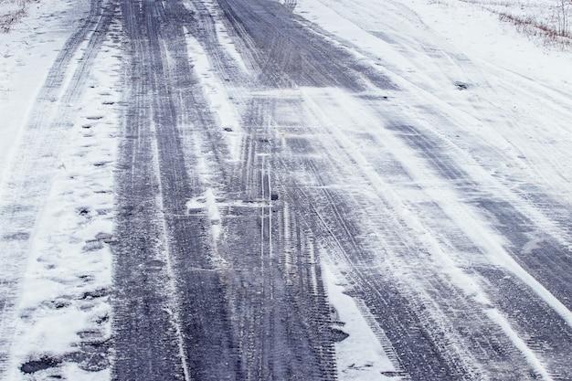 Traces de roues de voiture sur une route enneigée