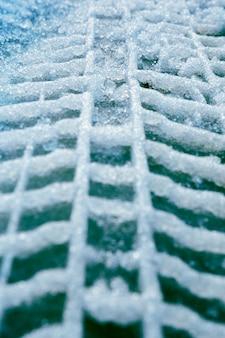 Traces verticales de pneus de voiture dans la neige sur l'asphalte.