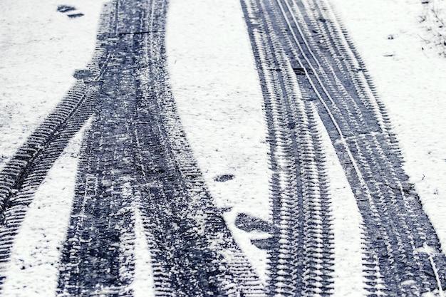 Traces d'une voiture et d'un homme dans la neige