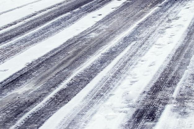 Traces de voitures sur neige mouillée, route d'hiver