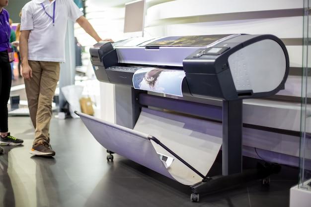 Le traceur imprime une affiche debout à côté de personnes en arrière-plan flou en gros plan flou