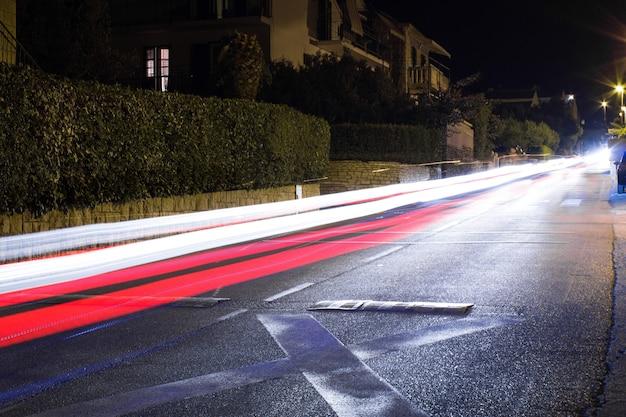 Traceurs des voitures qui passent. route de nuit avec des fantômes de lumières de voitures. exposition longue. fond.
