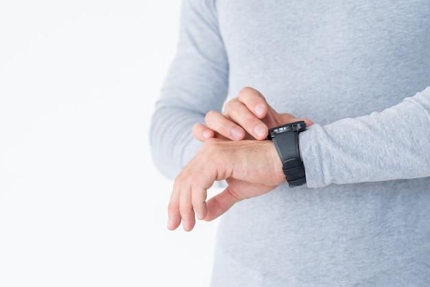 Le tracker de fitness est un gadget utile dans la vie de tous les jours. homme vérifiant sa fréquence cardiaque ou la distance qu'il a parcourue sur sa montre à main.