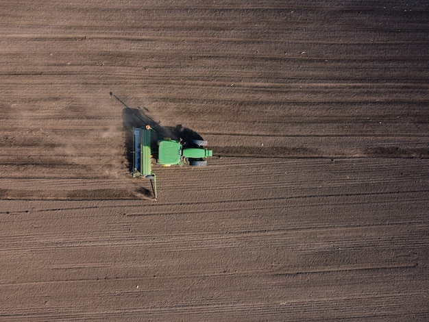 Tracteur agricole laboure le champ de sol pour le semis
