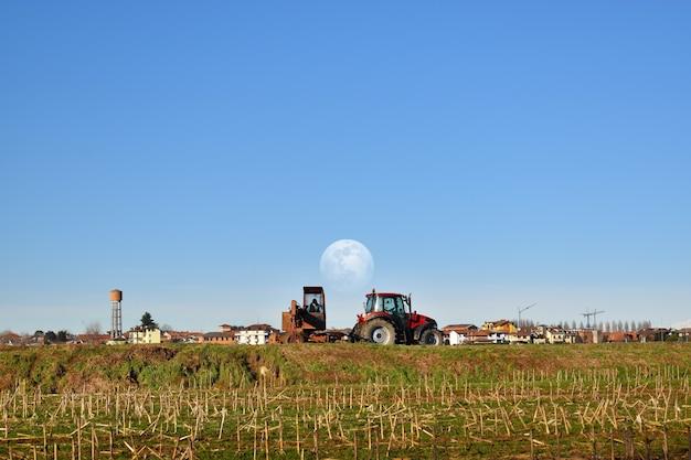 Tracteur au travail à la campagne avec la pleine lune dans le ciel