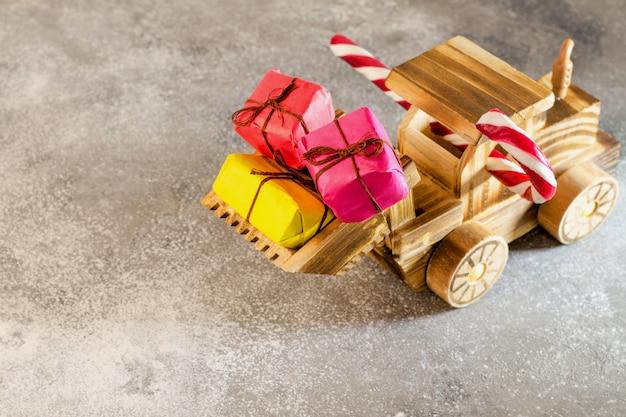 Un tracteur en bois transporte des cadeaux de noël dans son seau.