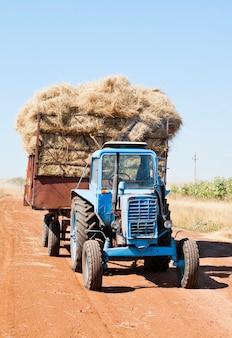 Tracteur avec chariot de foin sur une route de campagne