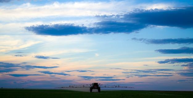 Un tracteur dans le champ pulvérise des champs au coucher du soleil une journée difficile pour le travailleur acharné