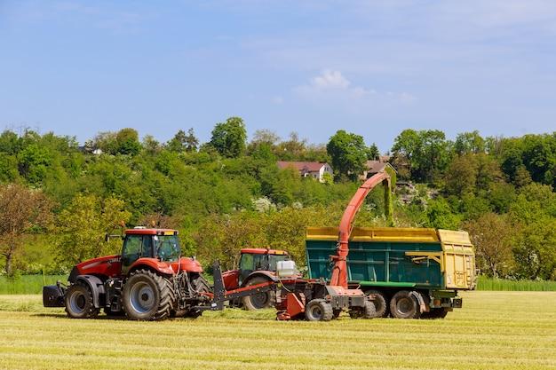 Un tracteur avec des ensileuses enlève l'herbe coupée du champ pour l'ensilage remplissant une remorque de tracteur par une journée ensoleillée.