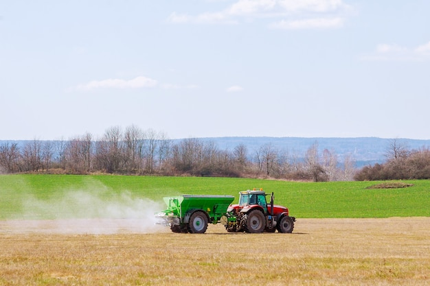Tracteur épandant des engrais sur terrain en herbe.
