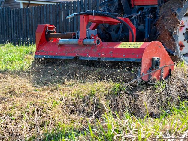 Un tracteur équipé d'une tondeuse broie l'herbe sèche le long de la clôture. traitement des parcelles