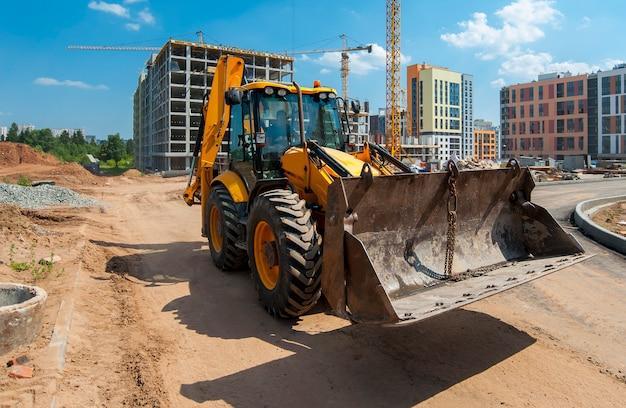 Tracteur jaune sur un chantier de construction définit les poteaux sur le terrain
