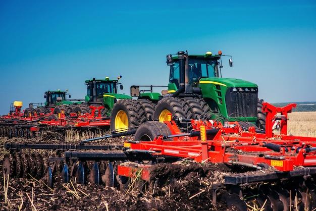 Tracteur labourant le champ de la ferme en préparation pour la plantation de printemps