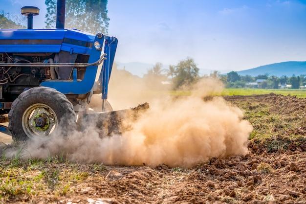 Tracteur labourant dans un champ agricole en saison agricole sur des collines