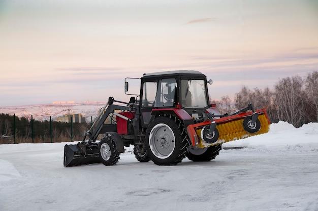 Un tracteur avec des outils montés enlève la neige sur la route de la ville