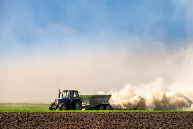 Tracteur pulvérisant de l'engrais sur le sol au début du printemps. maintenir la fertilité des sols, améliorer le développement des cultures