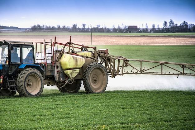 Un tracteur pulvérise un champ avec des suppléments de croissance et détruira les maladies des plantes. agriculture. fournir de la nourriture.