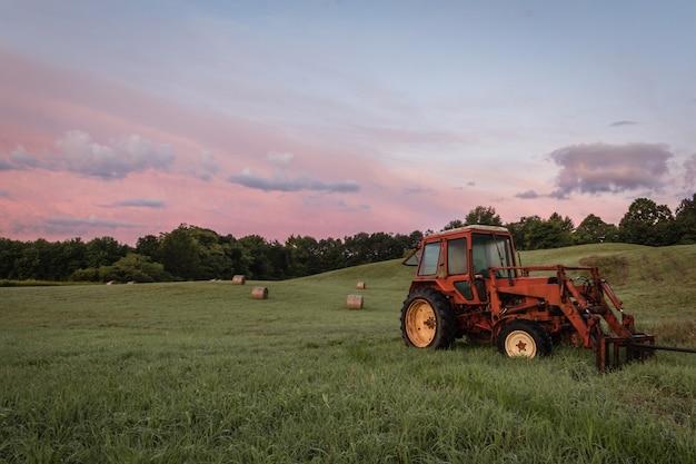 Tracteur rouge et balles de foin fraîchement roulées dans une terre agricole au coucher du soleil