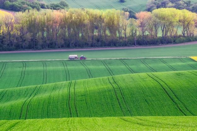 Le tracteur roule sur la route le long des champs verts, paysage agricole