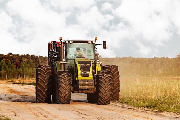 Tracteur sur une route à la campagne près des prés
