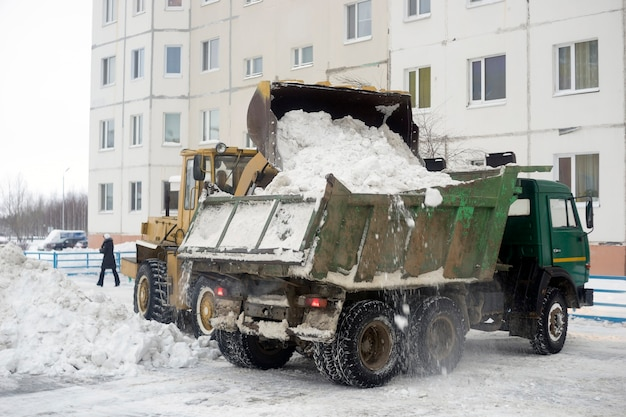 Le tracteur se charge dans la neige de la carrosserie de la voiture rassemblée dans la cour