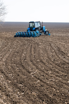 Tracteur sur le terrain sol noir au moment de la plantation
