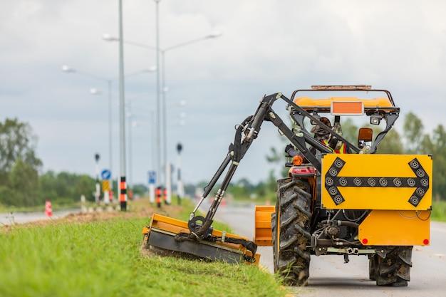 Tracteur avec une tondeuse mécanique tondant l'herbe sur le bord de la route goudronnée