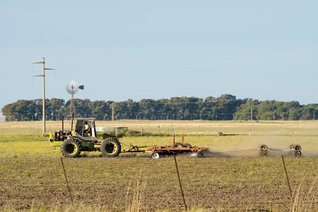 Tracteur traînant une herse dans un champ