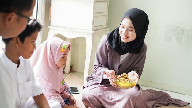 La tradition familiale de l'aïd al-fitr est de manger du ketupat opor ou des plats d'accompagnement