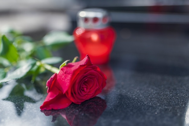 Tradition religieuse de mettre une fleur à la mémoire du défunt sur la dalle de granit du