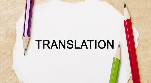 Traduction de texte sur un bloc-notes blanc avec des crayons sur un espace en bois