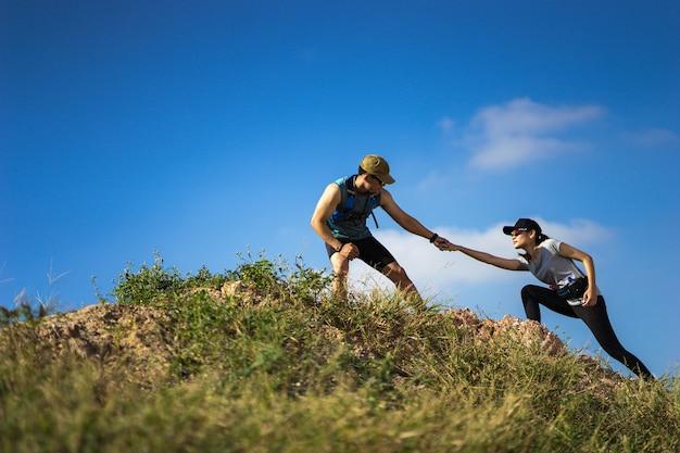 Trail runner aide les femmes à courir d'une pente