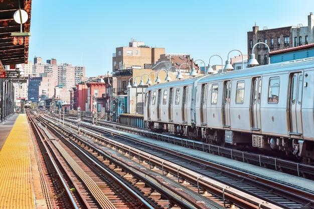 Train arrivant à la gare de new york. bâtiments en arrière-plan, paysage urbain. concept de voyage et de transit. manhattan, nyc, états-unis.