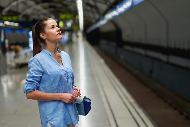 Train arrive - jeune femme en attente de sa connexion dans une gare moderne
