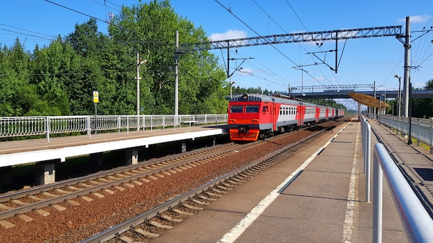 Train de banlieue arrive à la gare en été par journée ensoleillée. plate-forme ferroviaire avec train en route.