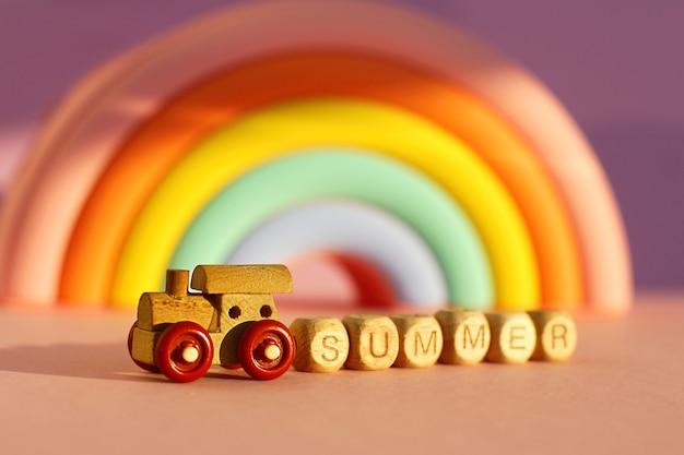 Un train en bois avec des cubes avec l'inscription été sur fond d'un volumineux arc-en-ciel lumineux. le concept de voyage et souhaite un bon voyage