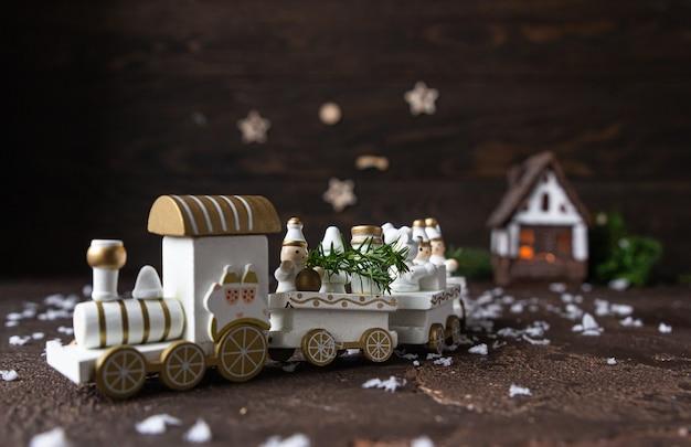 Train de bois de noël festif blanc et maison avec des branches de sapin en toile de fond