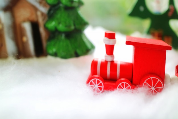 Le train en bois rouge en cours d'exécution sur la neige avec le pin et la maison en bois.