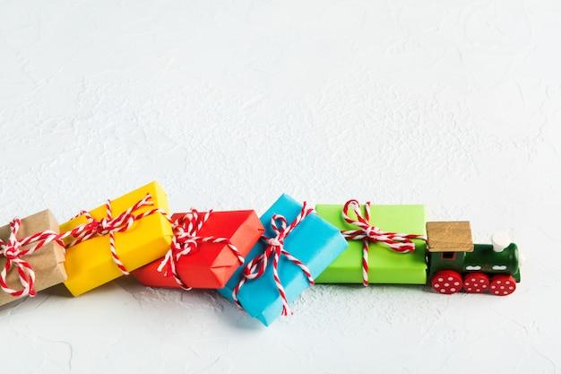 Train en bois vert transporter des cadeaux colorés de noël sur fond blanc, espace pour copie