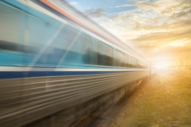 Train classique en mouvement avec coucher de soleil la gare ferroviaire environnement local classique train interurbain sur le chemin de fer. effet de flou de mouvement. vieux concept de vitesse de train.