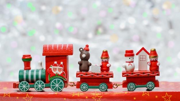Train jouet en bois rouge du père noël avec chariots, ours, bonhomme de neige et gnome.
