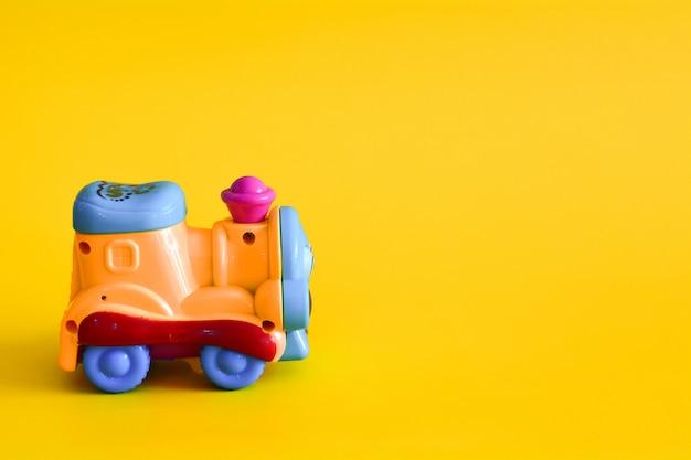 Train jouet sur fond jaune.