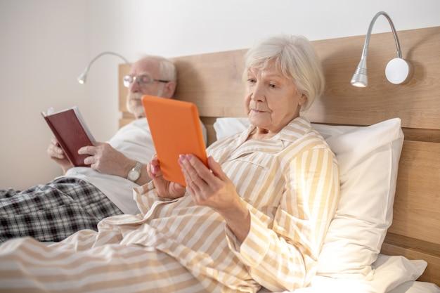 En train de lire. couple marié âgés au lit et lecture