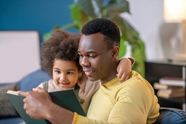 En train de lire. petite fille mignonne à la peau foncée bouclée serrant le jeune papa lisant un livre par le cou passer du temps libre ensemble à la maison sur un canapé