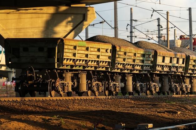 Train de marchandises sur rails wagons avec livraison de minerai de charbon en pierre concassée par chemin de fer