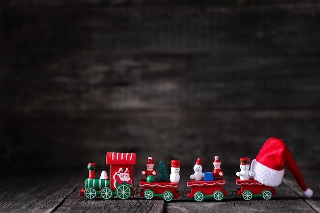 Train de noël avec chapeau de père noël gros plan sur fond de bois