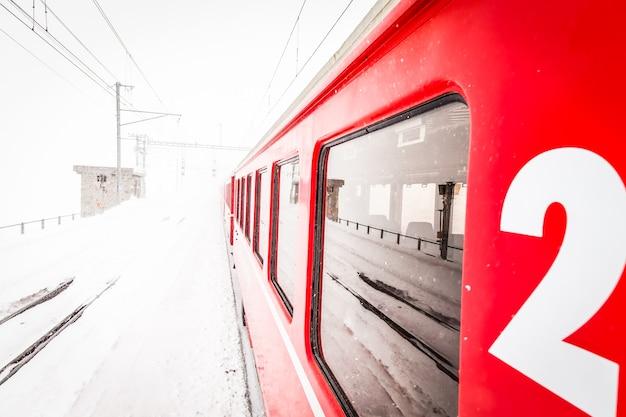 Un train rouge au milieu d'un désert de neige